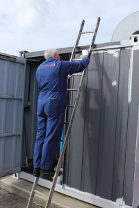 A painter painting a large container while working from a set of ladders